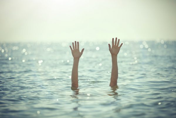 unrecognizable man hands waving for help, drowning into the sea.sunlight.horizontal shot.